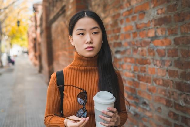Femme asiatique tenant une tasse de café.