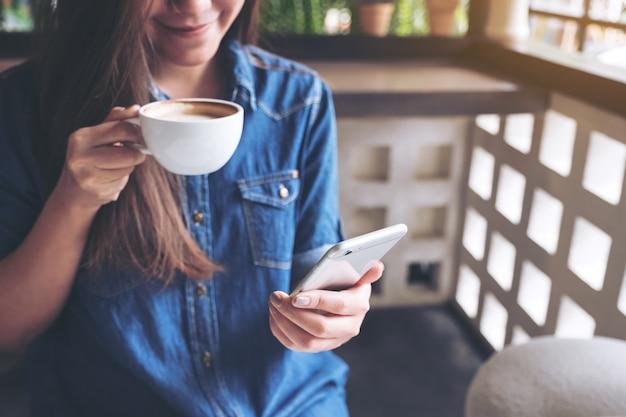 Une femme asiatique tenant un téléphone intelligent tout en buvant du café