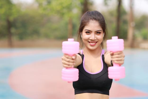 Femme asiatique en tenue de sport debout et soulevant des haltères en plein air pour l'exercice du matin.