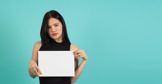 Une femme asiatique tient un carton vide vierge sur fond vert ou menthe ou bleu tiffany.
