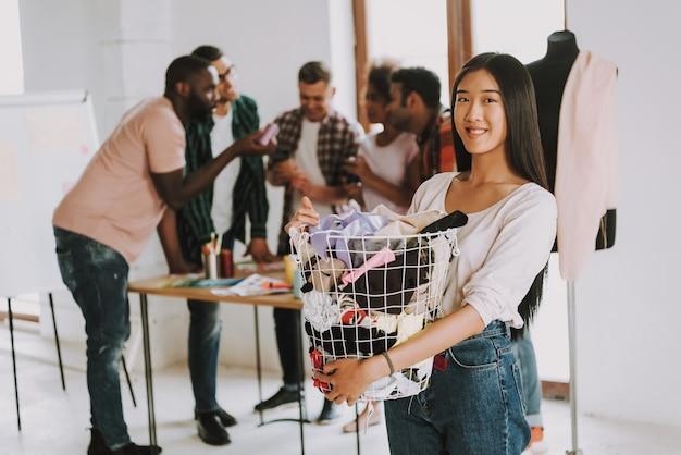 Femme asiatique tient un panier avec un chiffon.