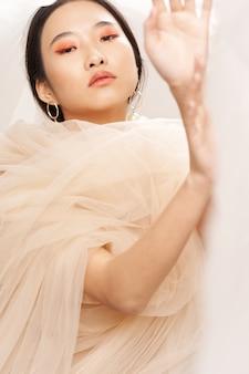 Femme asiatique avec un tissu transparent sur ses épaules faisant des gestes avec le maquillage des mains