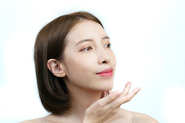 Femme asiatique touchant le visage sourire avec une peau saine isolé sur blanc