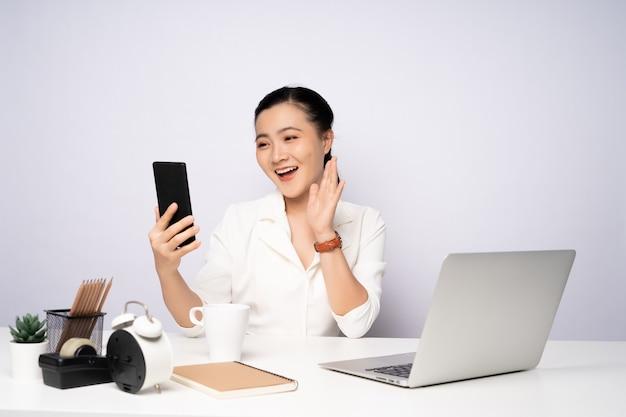Femme asiatique travaillant au bureau en utilisant un téléphone intelligent pour se détendre. affaires avec des concepts technologiques.