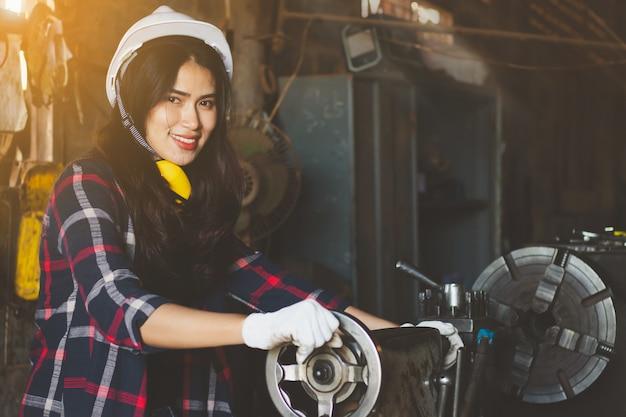 Femme asiatique travaillant dans l'usine, l'industrie à l'aide de machine à heureux.