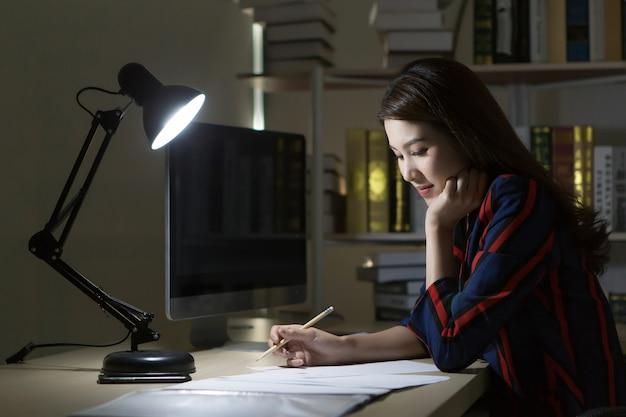 Femme asiatique travaillant à la maison la nuit en utilisant un ordinateur pour rechercher des informations en ligne.
