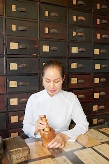 Femme asiatique travaillant à la pharmacie traditionnelle