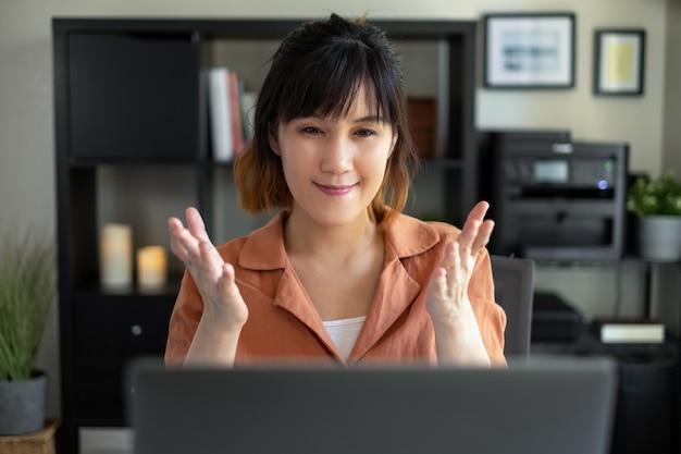 Femme asiatique travaille sur ordinateur portable au bureau à domicile. appel vidéo, étudier, apprendre et travailler en ligne.