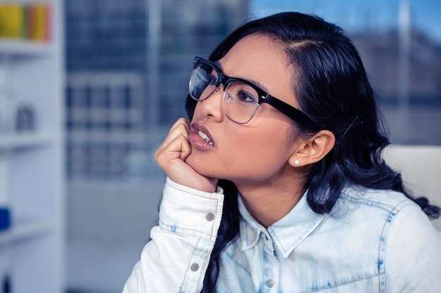 Femme asiatique troublée au menton sur le poing au bureau