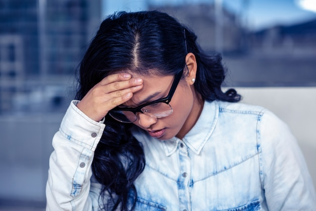 Femme asiatique troublée avec la main sur le visage au bureau