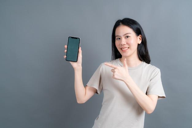 Femme asiatique utilisant des applications de téléphonie mobile, appréciant de communiquer à distance en ligne sur un réseau social ou de faire du shopping isolé sur fond gris