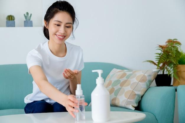 Une femme asiatique utilisant un gel désinfectant pour les mains à l'alcool se lave les mains pour se protéger du coronavirus lorsque la distance sociale reste à la maison pendant la quarantaine. concept d'hygiène et de soins de santé.