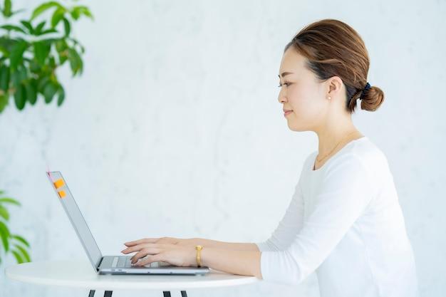 Femme asiatique utilisant un ordinateur portable dans une pièce lumineuse
