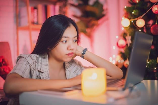Femme asiatique utilisant un ordinateur portable pour regarder les médias sociaux en ligne à la maison