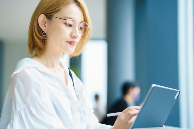 Femme asiatique utilisant un tablet pc dans la ville