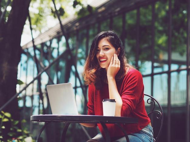 Femme asiatique utilisation d'un ordinateur portable lors de la consommation de café à l'extérieur.
