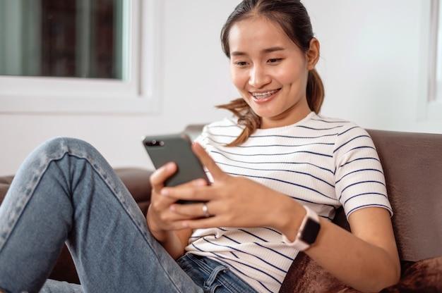 Femme asiatique, utilisation, téléphone portable, sur, sofa, et, sourire, chez soi