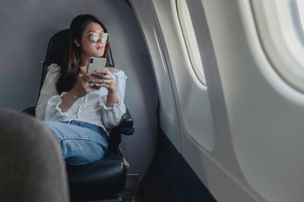 Une femme asiatique utilise un téléphone pour contacter ses parents avant d'éteindre le téléphone