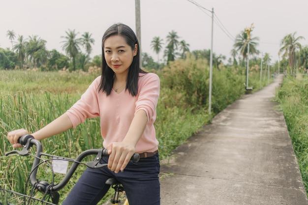 Femme asiatique à vélo dans la rue avec vue sur la verdure.