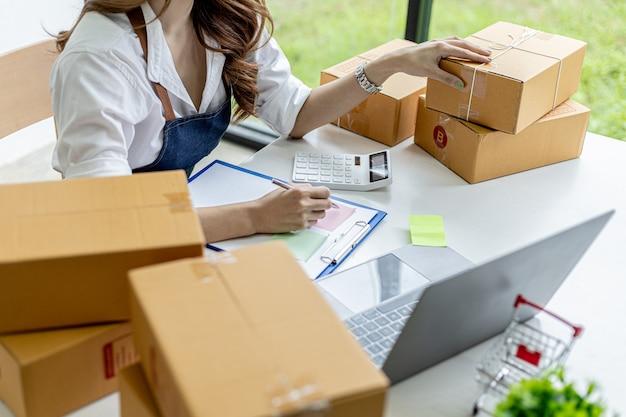 Femme asiatique vérifiant les boîtes de colis pour les clients, elle possède une boutique en ligne, elle prend les commandes des clients sur le site web et les envoie via un service de messagerie privé. concept de vente en ligne.