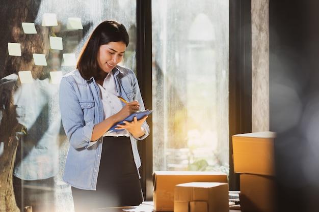 Femme asiatique vérifier les produits en stock avec intention et heureux.