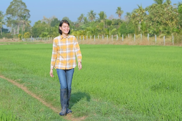 Une femme asiatique vêtue d'une chemise à rayures jaunes marchait souriant joyeusement dans le champ.