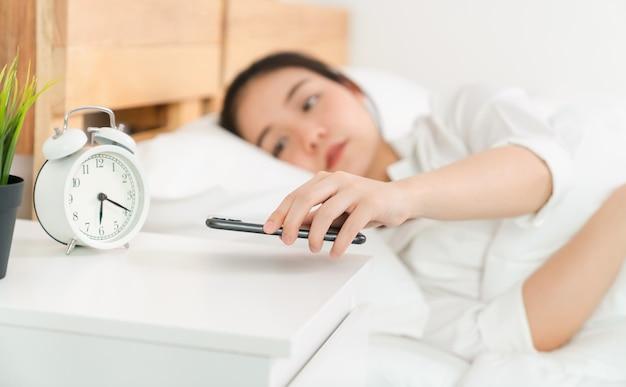 Une femme asiatique vient de se réveiller le matin et sur le lit, décrochant le téléphone pour vérifier ses réseaux sociaux.