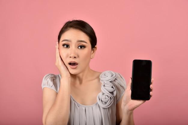 Femme asiatique avec un visage d'expression douteux et interrogateur tenant un smartphone, de fausses nouvelles et une désinformation de canular se propageant via les médias sociaux internet.