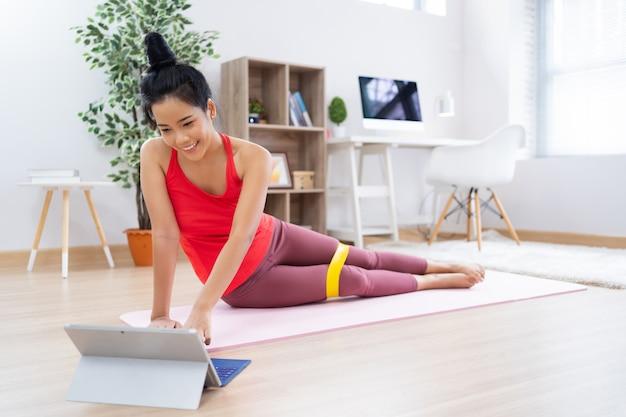 Femme asiatique voir les méthodes d'exercice de la tablette.