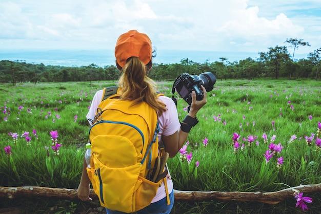 Femme asiatique voyage nature. voyage relax. photographie champ de fleurs de sessilis de concombre.