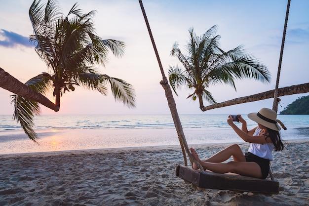 Femme asiatique voyageur à l'aide de téléphone mobile et se détendre sur la balançoire dans la plage tropicale au coucher du soleil koh kood thaïlande
