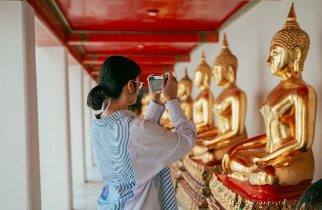 Femme asiatique voyageur prendre photo ancienne statue de bouddha