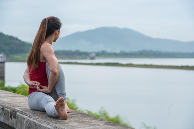 Femme asiatique en yoga pose sur le mur au bord du lac.