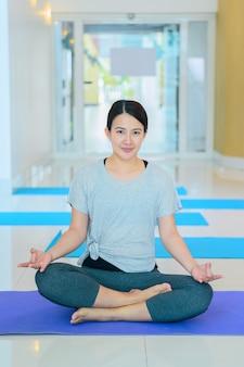 Femme asiatique yoga respiration et méditation seule dans une salle de fitness. exercices d'intérieur et entraînement pour la santé et le bien-être.