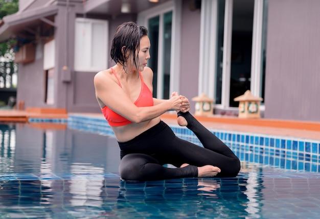 Femme asiatique yoga respiration et méditation seule à la piscine à la maison. exercice et entraînement en plein air pour la santé et le bien-être.