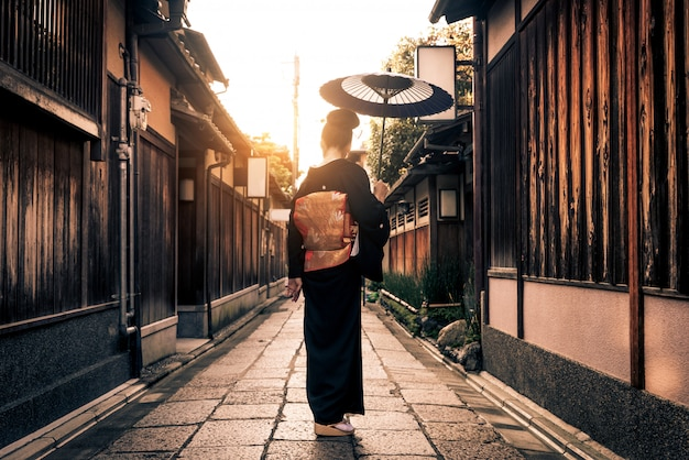 Femme asiatique avec yukata marchant à kyoto, japon