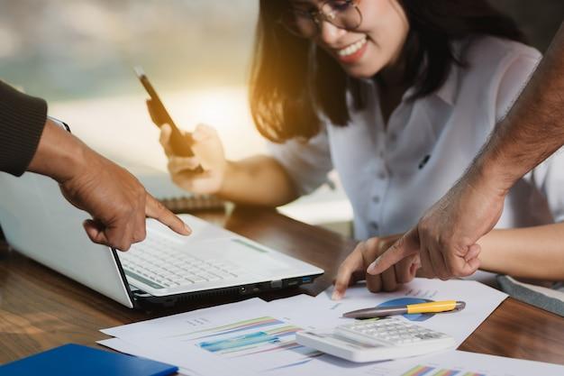 Femme d'asie à l'aide de smartphone, ordinateur personnel travaillant avec des amis avec bonheur.