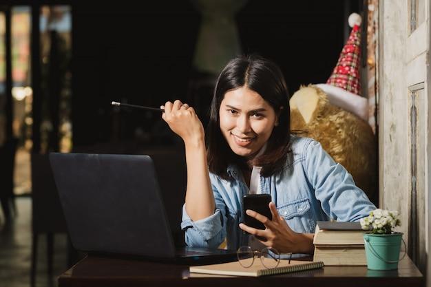 Femme d'asie à l'aide de smartphone, ordinateur personnel travaillant avec heureux.