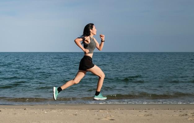 Femme d'asie en articles de sport exerçant et en cours d'exécution sur la plage.