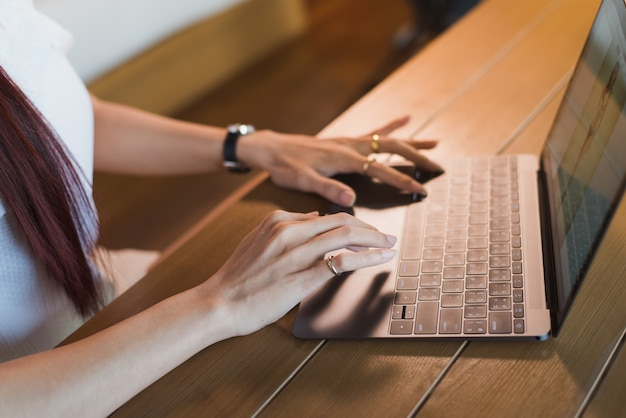 Femme d'asie avec un ordinateur portable assis à la table