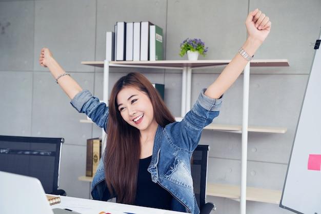 Femme asie avec ordinateur portable célébrant le concept de succès ou le concept d'entreprise de démarrage