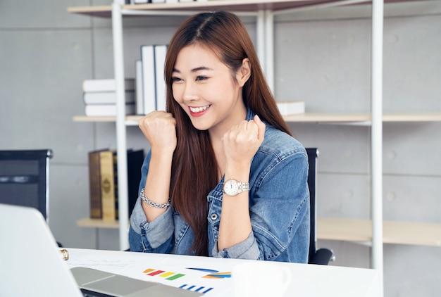 Femme asie avec ordinateur portable célébrant le concept de succès