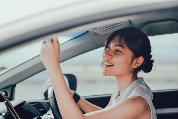 Femme asisn détendue souriante regardant dans le rétroviseur. s'asseoir sur la voiture. concept de mode de vie et de personnes.