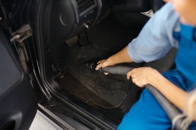 Femme avec aspirateur, service de lavage de voiture