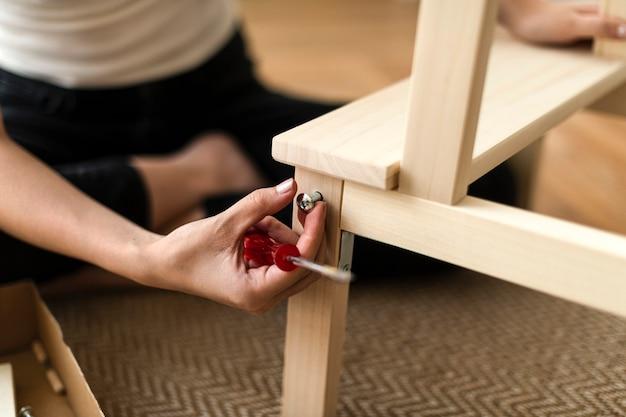 Femme assemblant une chaise de bricolage à partir de zéro