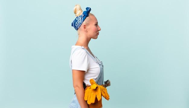Femme assez blonde sur la vue de profil pensant, imaginant ou rêvant et réparant le concept de maison
