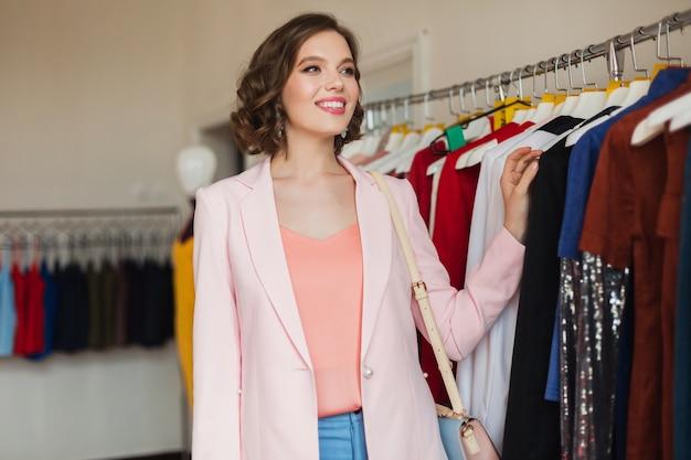 Femme assez élégante en choisissant des vêtements en boutique