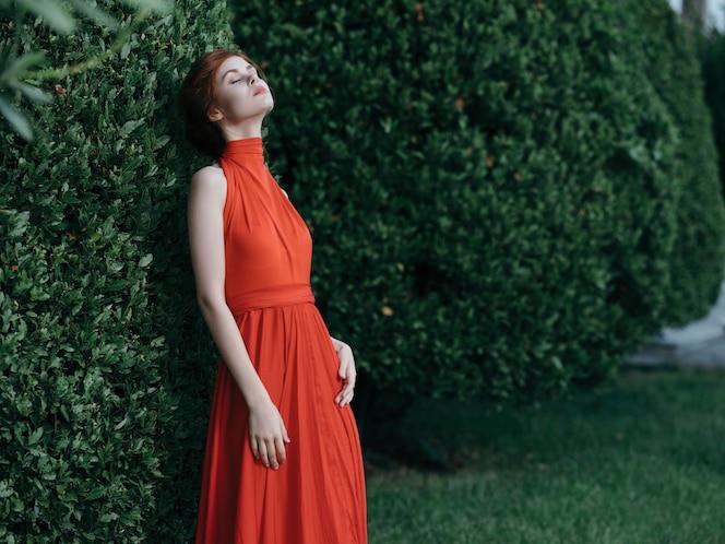 Femme assez élégante en robe rouge dans le carnaval de style gothique de jardin
