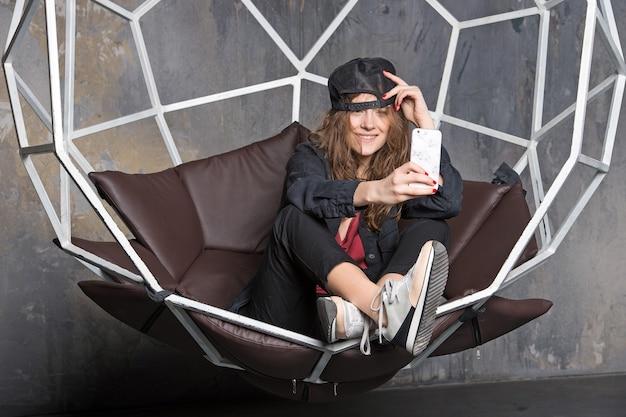 Femme assez heureuse ou jolie fille sexy aux cheveux longs en casquette noire et baskets assis dans une chaise géométrique faisant selfie sur mobile ou téléphone portable sur fond gris