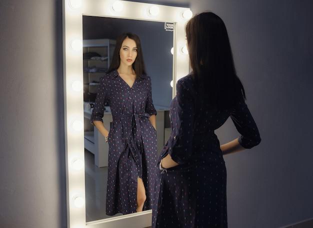Femme assez heureuse regardant sur elle-même dans un grand miroir. la femme choisit une tenue pour les vacances